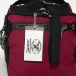Red Oxx Vinyl Luggage tag shown on a Red Oxx Beano Bag
